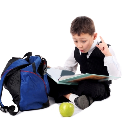 schoolboy with book and apple isolated on white